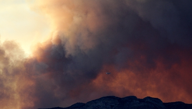 A plane flies over the Carpenter 1 fire near Las Vegas on Monday. The Carpenter 1 Fire has spread to more than 14,000 acres and is the second highest priority wildfire in the nation.