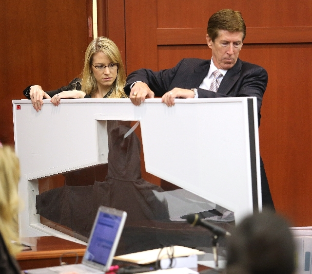 Defense counsel Mark O'Mara and an assistant carry  Trayvon Martin's hooded sweatshirt in the George Zimmerman trial in Seminole Circuit Court, in Sanford, Fla., Tuesday. Zimmerman is charged with ...
