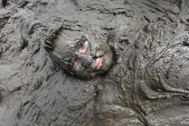 Zach Miller, 10, of Livonia lies in mud in Westland, Mich., Tuesday.