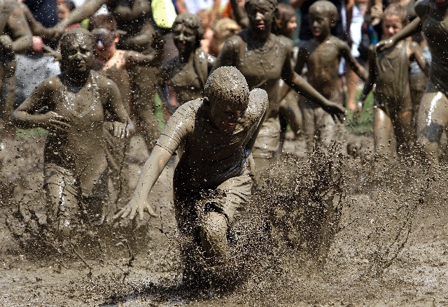 Logan Palshan, 12, of Taylor runs in the mud in Westland, Mich., Tuesday.