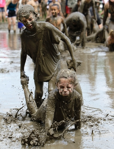 Stephanie Strong, 9, standing, helps Grace Lipscomb, 10, both of Howell, wheel barrow in the mud in Westland, Mich., Tuesday.
