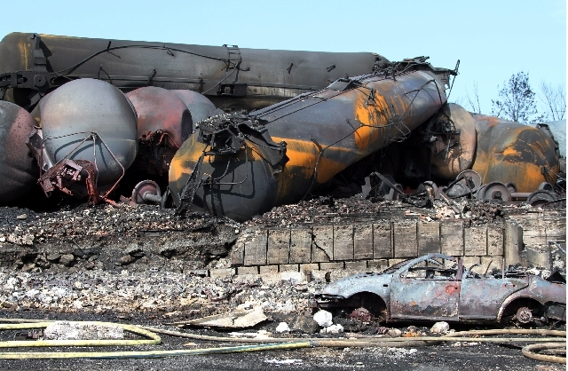 This photo provided by Surete du Quebec, shows wrecked oil tankers and debris  from a runaway train on Monday in Lac-Megantic, Quebec, Canada.  A runaway train derailed igniting tanker cars carryi ...
