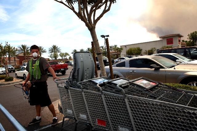Jason Moore, 17, wears a mask protect to himself from the smoke produced by the Carpenter 1 fire, seen in background at right, while working in northwest Las Vegas Tuesday. The wildfire, which has ...