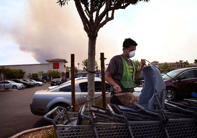 Jason Moore, 17, wears a mask protect to himself from the smoke produced by the Carpenter 1 fire, seen in background at left, while working in northwest Las Vegas Tuesday. The wildfire, which has  ...