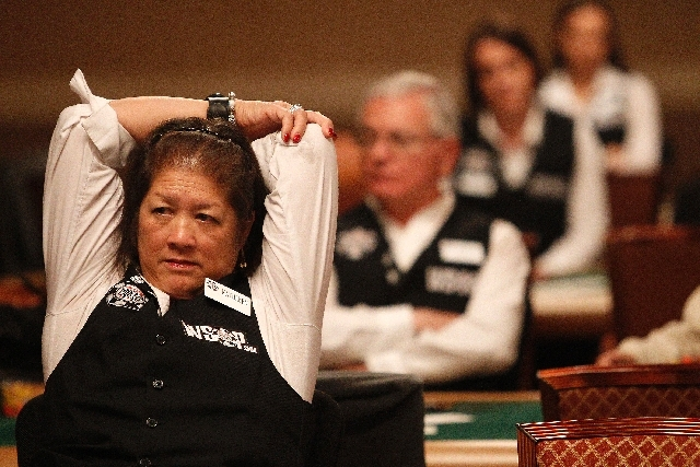 Dealer Kathleen Sheng Congdon stretches during a break in the main event at the World Series of Poker at The Rio in Las Vegas Tuesday.