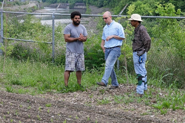 Chris Cerveny, center, Scotts Miracle-Gro representative,with volunteers Jonathan Sears, left, and Lennell Myricks Jr.  looks over a garden that was planted next to Mill Creek, seen in the backgro ...