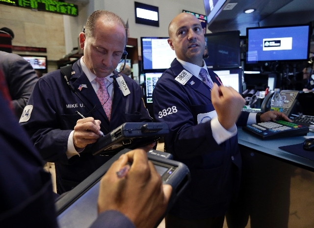 Specialist Frank Babino, right, and trader Michael Urkonis works on the floor of the New York Stock Exchange Wednesday. Stocks nudged higher in early trading Wednesday before the Federal Reserve r ...