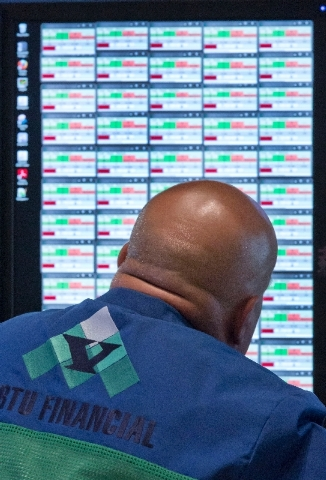 A specialist watches his screen as he works on the floor of the New York Stock Exchange Wednesday. Stocks nudged higher in early trading Wednesday before the Federal Reserve releases minutes from  ...