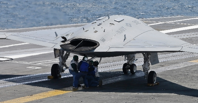 Navy crew members manually list the tailhook of A X47-B Navy after it landed  aboard the nuclear aircraft carrier USS George H. W. Bush off the Coast of Virginia Wednesday. It is the first landing ...