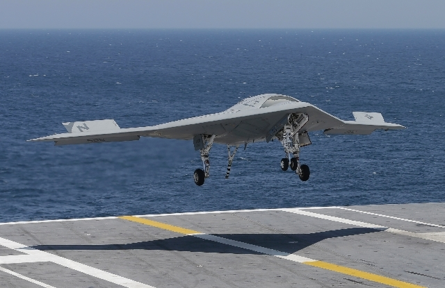 A X47-B Navy drone approaches the deck as it lands aboard the nuclear aircraft carrier USS George H. W. Bush off the Coast of Virginia Wednesday. It is the first landing by a drone on a Navy carri ...