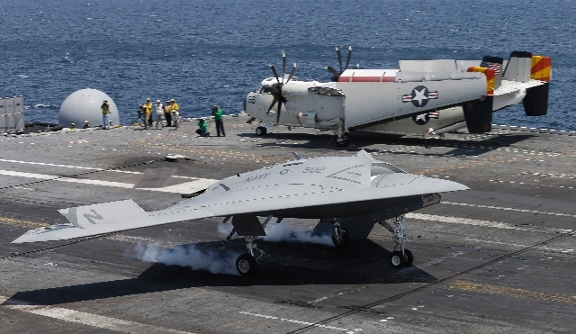 A X47-B Navy drone touches down as it lands aboard the nuclear aircraft carrier USS George H. W. Bush off the Coast of Virginia Wednesday. It is the first landing by a drone on a Navy carrier.  Th ...