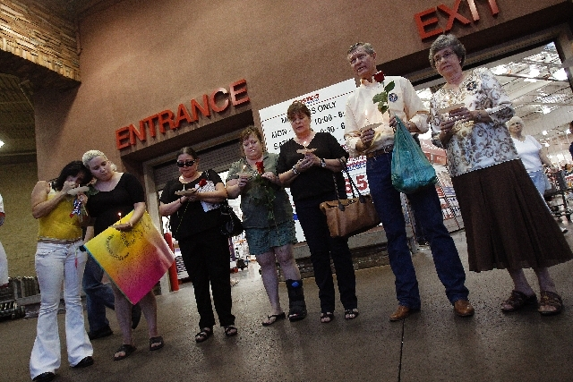 Linda Scott, right, and her husband Bill Scott, second from right, attend a vigil for Erik Scott at the Summerlin Costco in Las Vegas Wednesday. Erik Scott, son of Bill and Linda Scott, was killed ...