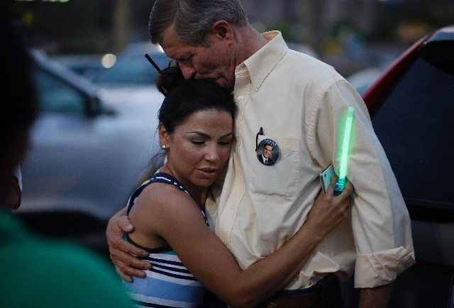 Violet Abreo-Frear, left, hugs Bill Scott at during a vigil for Erik Scott at the Summerlin Costco on Wednesday. Erik Scott, son of Bill Scott, was killed by Las Vegas police three years ago at th ...