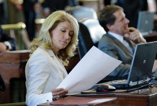 Sen. Wendy Davis, D-Fort Worth, looks over papers in the Senate Chambers on Thursday.