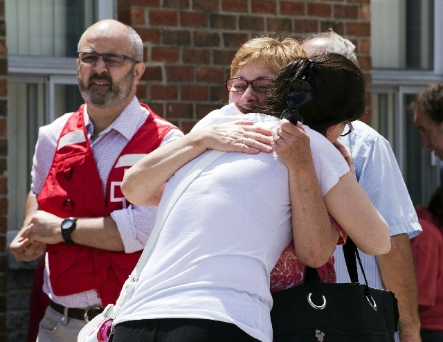 People hug outside an emergency shelter for evacuees in Lac-Megantic, Quebec, Thursday. The shelter is set up for the affected by the derailment and explosion of an oil train July 6.