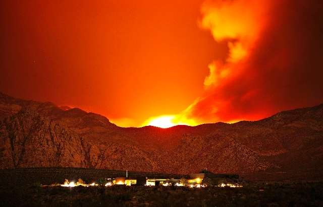 The Carpenter 1 Fire burns in the mountains behind the Red Rock Conservation Area visitor center near Las Vegas early in the morning of Thursday, July 11. The fire has forced the closure of the Re ...