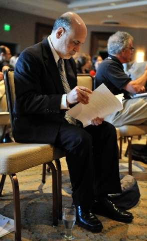 Federal Reserve Board Chairman Ben Bernanke reads some notes before speaking to the National Bureau of Economic Research Wednesday, July 10, 2013, in Cambridge, Mass. Bernanke spoke after the mark ...