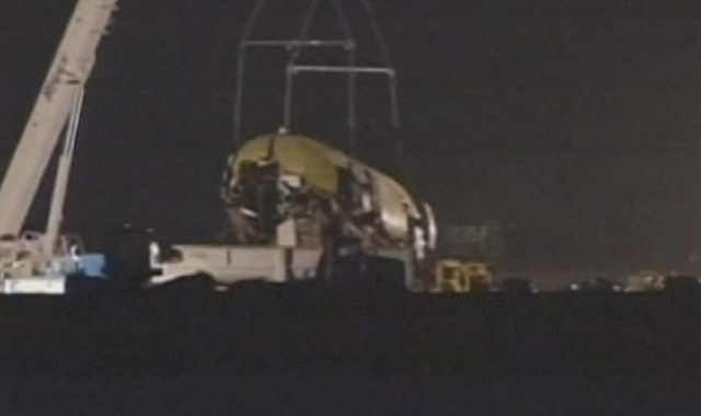 In this image from video provided by ABC7 News/KGO-TV a section of the fuselage of Asiana Flight-214 is removed at San Francisco airport early Friday morning. Workers began clearing the wreckage e ...