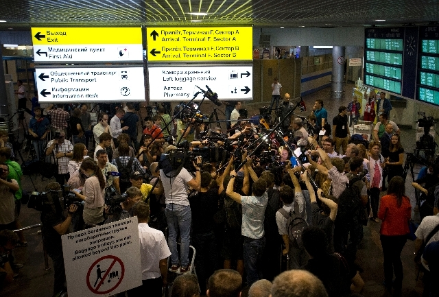 Journalists gather around Genri Reznik, a prominent lawyer and head of the Moscow bar association, at Sheremetyevo airport outside Moscow, Russia, Friday. Two prominent Russian human rights offici ...