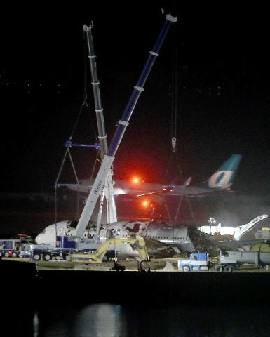 A plane lands at San Francisco International Airport as Asiana flight 214 is dismantled and prepared to be hauled to a hangar in San Francisco, Calif., on Friday.