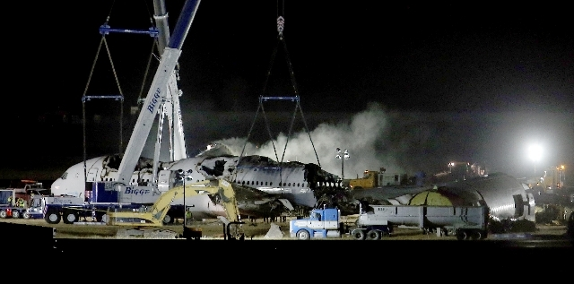 Smoke is seen as Asiana flight 214 is dismantled and prepared to be hauled to a hangar at San Francisco International Airport in San Francisco, Calif., on Friday.