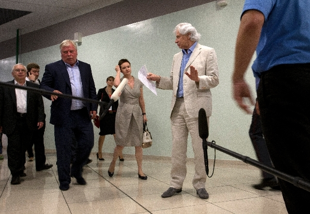 Lawyers Genri Reznik, right, and Anatoly Kucherena, left front, walk after meeting National Security Agency leaker Edward Snowden at Sheremetyevo airport outside Moscow, Russia, Friday.