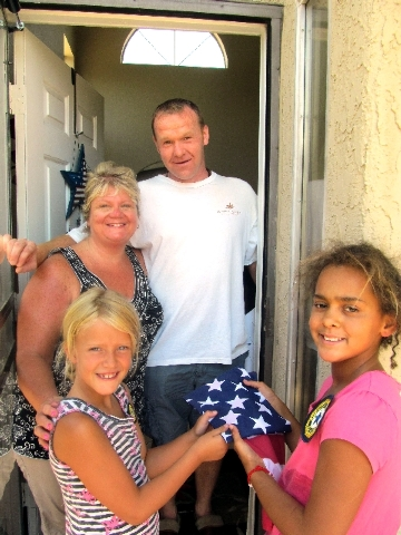 Sage Nulty, 7, left, Kiara Woodstock, 10, and adults Eileen Lannon and Seamus Lannon take a break from handing out American flags on July 4. The children are members of the American Legion Auxilia ...