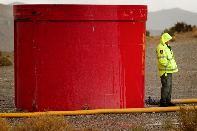 Las Vegas Metropolitan police officer Jim Pendleton stands beside helicopter dip tank while rain falls at the 12 mile marker on the Kyle Canyon Road on Friday. Firefighting helicopters pick up ret ...