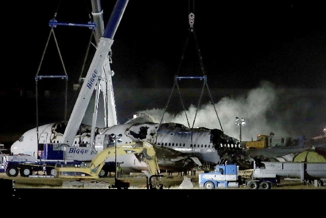 Asiana Airlines flight 214 is dismantled and hauled to a hangar at San Francisco International Airport in San Francisco on Friday. A San Francisco Bay Area TV station has apologized after reportin ...