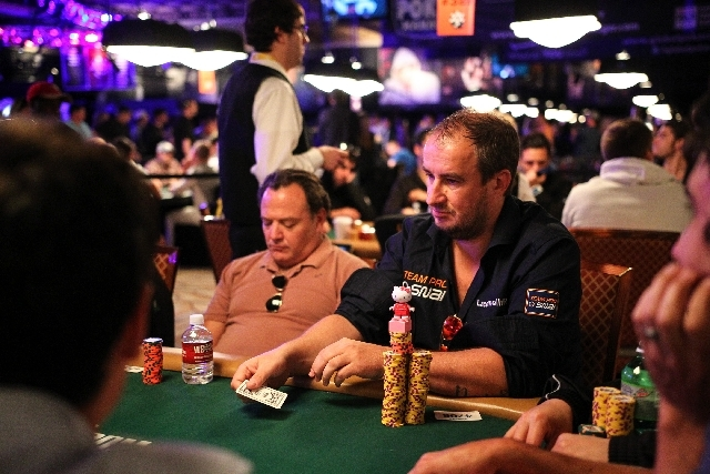 Ricardo Lacchinelli, center right, is seen as a Hello Kitty figurine sits atop his chips during the fourth day of the World Series of Poker Main Event at the Rio Convention Center in Las Vegas on  ...