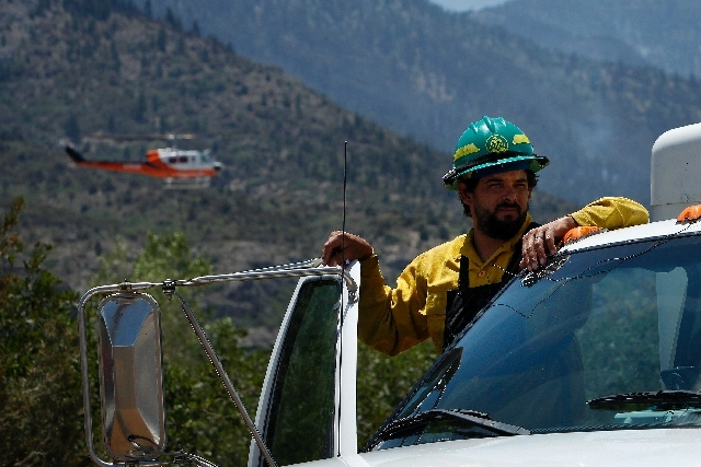 Steve Felix of Woods Fire and Emergency Services stands on his truck as a firefighting helicopter lands behind him while working the Carpenter 1 Fire in Kyle Canyon on Mount Charleston on Saturday.