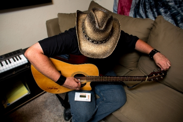 Henderson singer/songwriter Erick Martin tunes his guitar prior to a recording studio session July 14. Martin recently signed with Reformatory Records. His CD is set to come out in the fall, and h ...