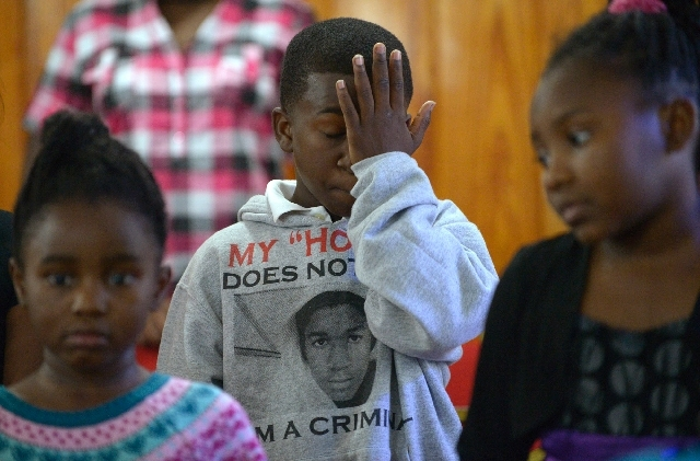 Sam Hill, 11, wipes tears Sunday at a service at St. Paul Missionary Baptist Church in Sanford, Fla. Many wore shirts in support of Trayvon Martin after George Zimmerman's not guilty verdict.