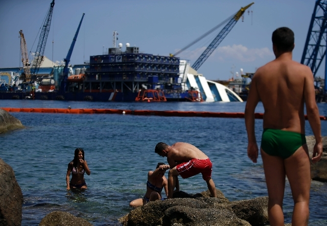 Sunbathers walk on rocks as the Costa Concordia cruiser is visible in background, in the Tuscan Island of Isola del Giglio, Monday.