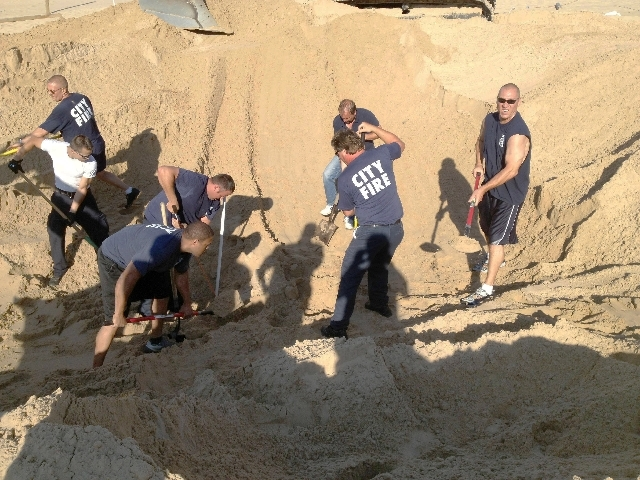 In this July 12 photo, Michigan City police and firefighters dig with shovels to rescue Nathan Woessner, of Sterling, Ill., who was trapped for more than three hours under about 11 feet of sand at ...