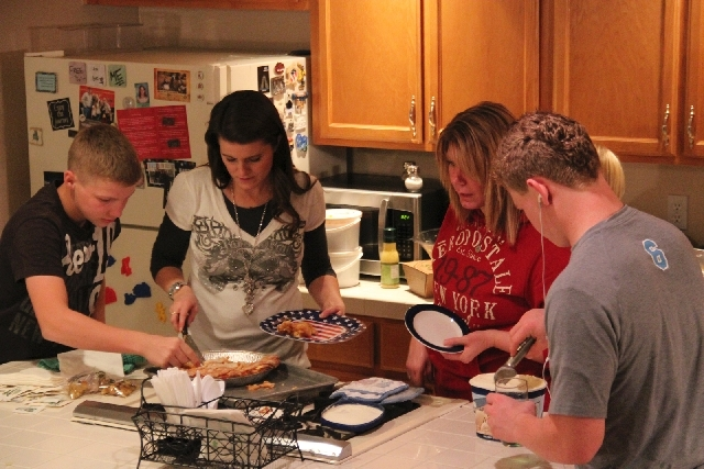Sister wives Robyn and Meri work in the kitchen, helped by two of the polygamist family's 17 children, sons Garrison, left, and Hunter. The family left Lehi, Utah, for Las Vegas in 2011.