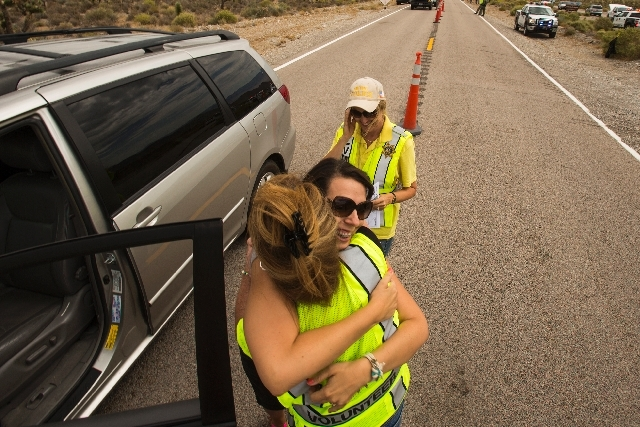 Lee Canyon resident JaeAnn Bernhardt hugs Las Vegas police volunteer Linda Fleming, left, while Lauren Olson looks on Monday at the Lee Canyon checkpoint. Lee Canyon residents were allowed to retu ...