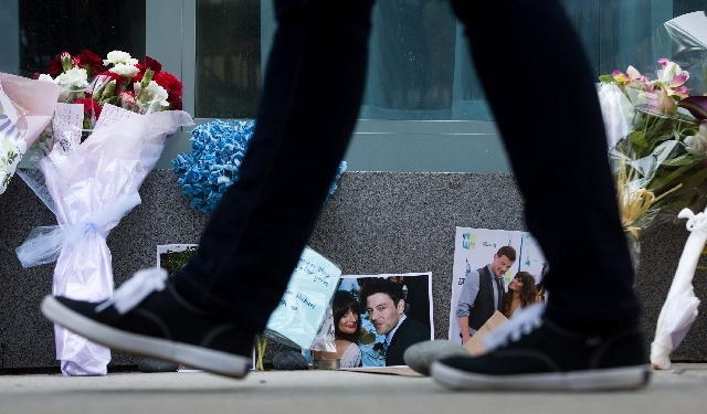 A pedestrian walks past photographs and flowers placed at a memorial for Canadian actor Cory Monteith outside the Fairmont Pacific Rim Hotel in Vancouver, British Columbia on Monday. Monteith, 31, ...