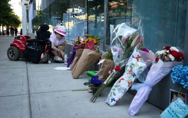 Amelia Cooper places flowers and a card at a memorial for Canadian actor Cory Monteith outside the Fairmont Pacific Rim Hotel in Vancouver, British Columbia on Monday. Monteith, 31, was found dead ...