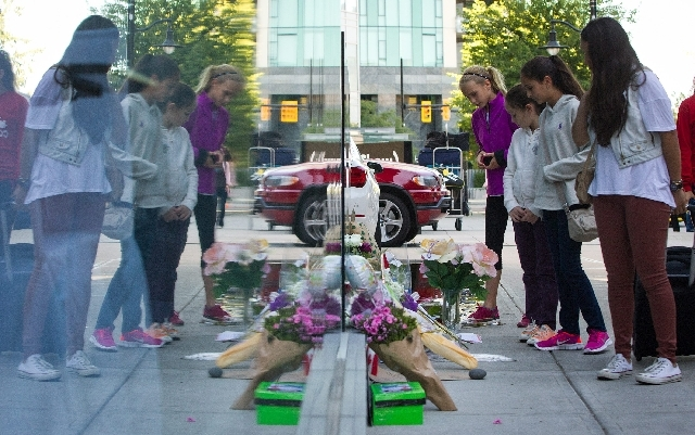 A woman reacts upon finding out Canadian actor Cory Monteith died as she pauses at a memorial for him outside the Fairmont Pacific Rim Hotel in Vancouver, B.C., on Monday. Monteith's body was foun ...