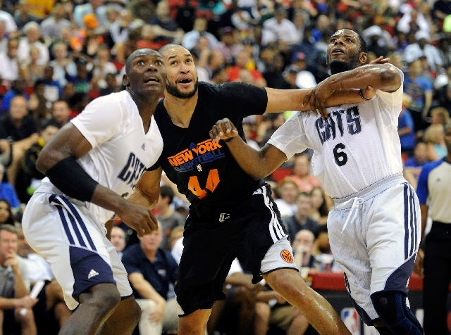 New York Knicks' Jerome Jordan, center, and Charlotte's Bismack Biyonbo, left and Patrick Ewing Jr. wear new style jerseys as they battle for a rebound during a NBA Summer League basketball game a ...