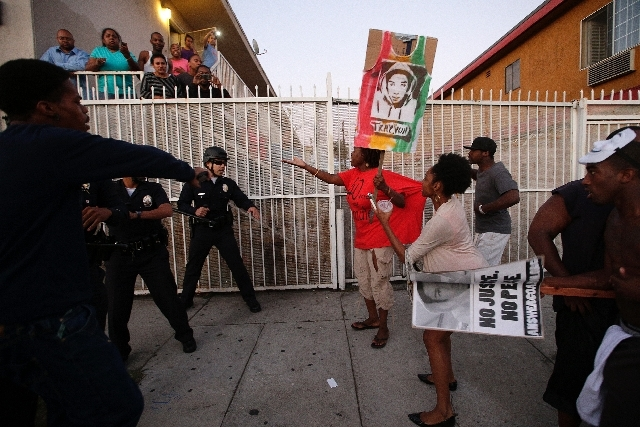 A protester holds up a sign while marching down a Los Angeles street Monday in reaction to the acquittal of George Zimmerman.