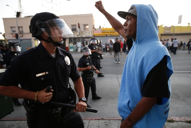 A protester confronts a Los Angles police officer on Monday during a demonstration in reaction to the acquittal of George Zimmerman. Anger over the acquittal of Zimmerman, who shot and killed Tray ...