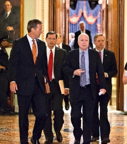 From left, Sen. John Thune, R-S.D., Sen. John Barrasso, R-Wyo., Sen. John McCain, R-Ariz., and Sen. John Hoeven, R-N.D., walk from the floor to a closed-door caucus after a compromise between the  ...