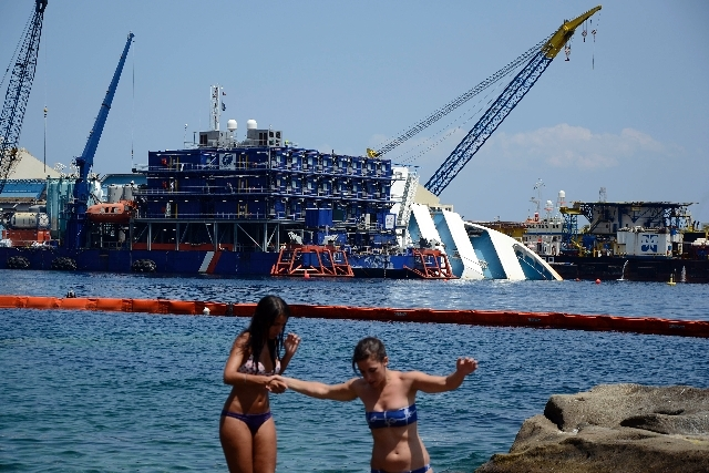 Sunbathers walk on rocks as the Costa Concordia cruiser is visible in background, in the Tuscan Island of Isola del Giglio, Monday. Salvage crews are working against time to right and remove the s ...