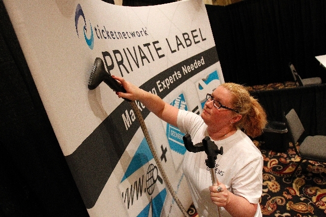 Sarah McComb steams a backdrop for a booth at The Ticket Summit at the Bellagio in Las Vegas Tuesday.