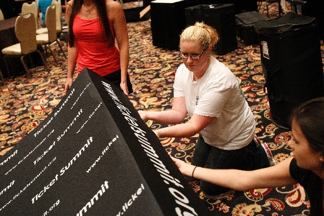 Sarah McComb, in white, helps to prepare a backdrop for a booth at The Ticket Summit at the Bellagio in Las Vegas Tuesday.