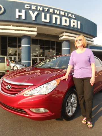 Ali Schagel poses by her 2013 Hyundai Sonata purchased from Planet Hyundai Centennial.