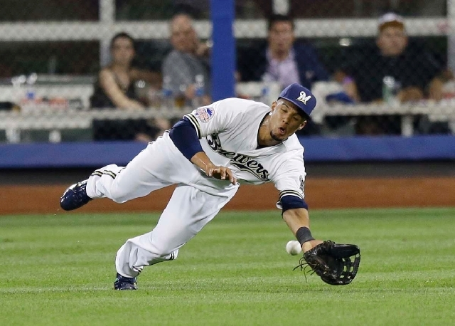 The National League's Carlos Gomez, of the Milwaukee Brewers, dives to reach a triple by American League's Prince Fielder, of the Detroit Tigers, during the ninth inning of the MLB All-Star baseba ...