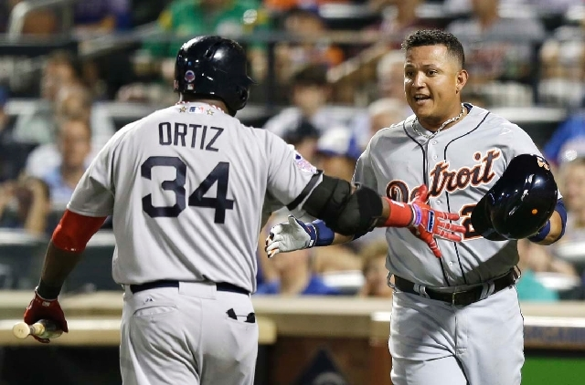 The American League's Miguel Cabrera, of the Detroit Tigers, is congratulated by David Ortiz, of the Boston Red Sox, after scoring on Toronto Blue Jays' Jose Bautista's sacrifice fly during the fo ...